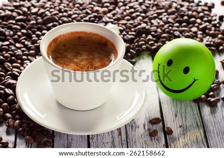 Fragrant, natural coffee in a cup standing on a wooden table in the coffee beans. Next to the cup is a little ball of green in the form of a smiley - stock photo