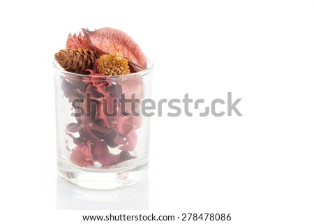 Fragrant natural potpourri with dried flowers, leaves and spices in a glass container on white background  - stock photo