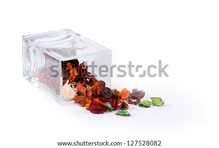 Fragrant natural potpourri with dried flowers, leaves and spices spilling out of a rectangular glass container onto a white background for that special fragrance in the house - stock photo