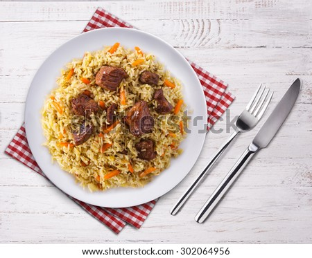 Fragrant pilaf with meat and vegetables close up on a plate. Top view on wooden table. Fork, knife and towel. - stock photo