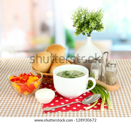 Fragrant soup in cup on table in kitchen