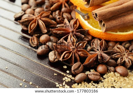 Fragrant spices, coffee, dry orange and reed sugar on a wooden background - stock photo