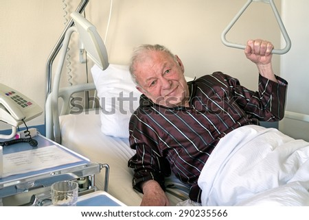 Frail senior man in a hospital bed propping himself up on one elbow to give the camera a wan smile in a medical and health care concept - stock photo