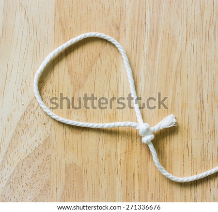 Frame composed of Rope on a Wooden background