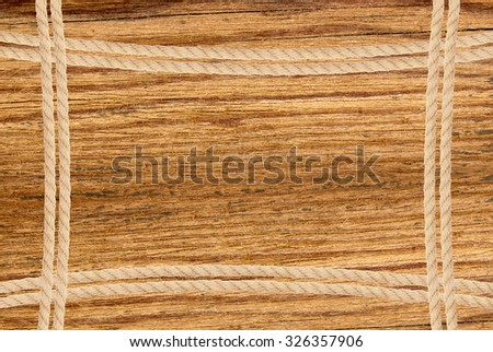 Frame composed of rope over wooden background - stock photo