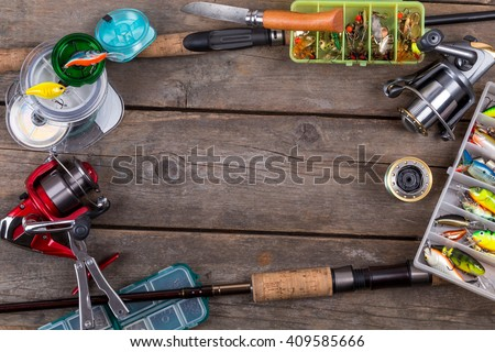 frame fishing tackles and fishing baits in box on wooden board background. Design for outdoor sport business - templates, web, poster, card, advertisement.