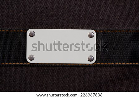 Frame for your text - closeup of blank white grungy artificial leather label with yellow metal rivets - stock photo