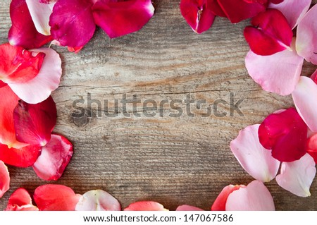 frame from petals of roses on a wooden background - stock photo