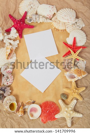 Frame from starfishes and cockleshells with two blank card on old paper - stock photo
