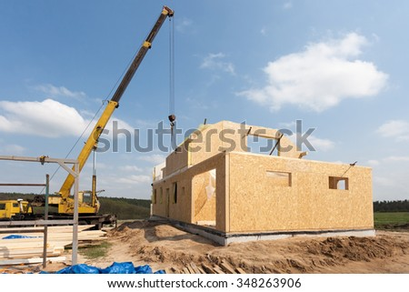 Frame house construction. View on new building with crane against blue sky - stock photo