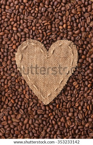 Frame in the shape of heart made of burlap with coffee beans, with space for your text - stock photo