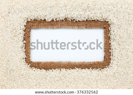 Frame made of burlap and rice grains lies on white background, with place for your creativity, text