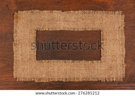Frame made of burlap  lying on a wooden surface, with space for your text - stock photo