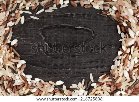 Frame made of colorful blend of rice varieties : brown rice, mixed wild rice, white (jasmine) rice in a rustic wooden surface background - stock photo