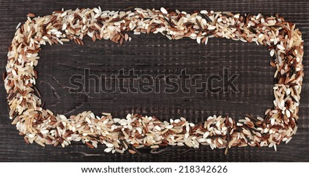 Frame made of colorful blend of several varieties of whole grain rice in a rustic wooden surface background - stock photo