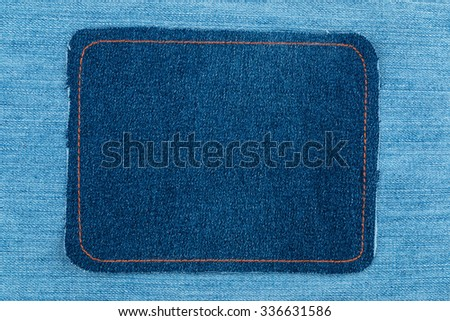 Frame made of denim with yellow stitching is on a light jeans, as a background