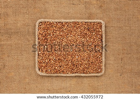 Frame made of rope with buckwheat grains on sackcloth, with place for your creativity - stock photo