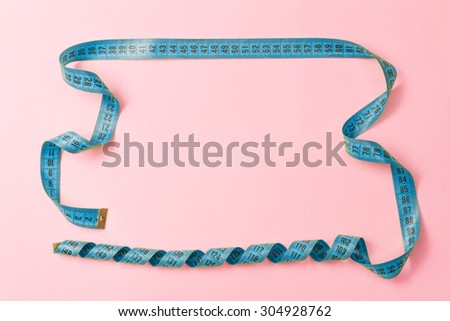 Frame made of tailor measuring tape on pink background with copy space - stock photo