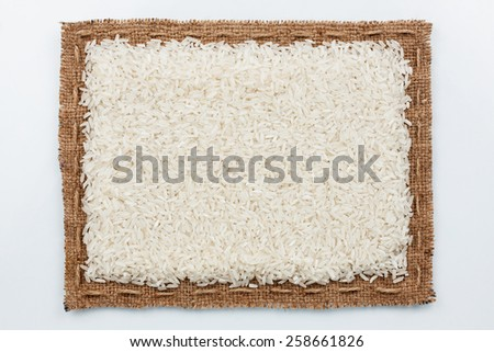Frame of burlap and rice grain, lying on a white background - stock photo