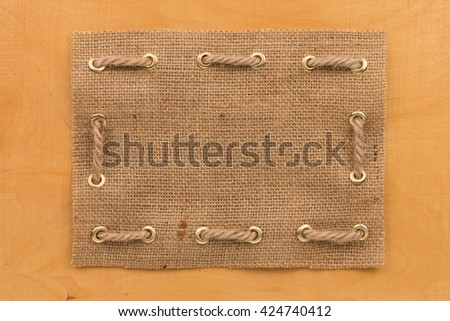 Frame of burlap, lying on  wooden, can be used as texture - stock photo