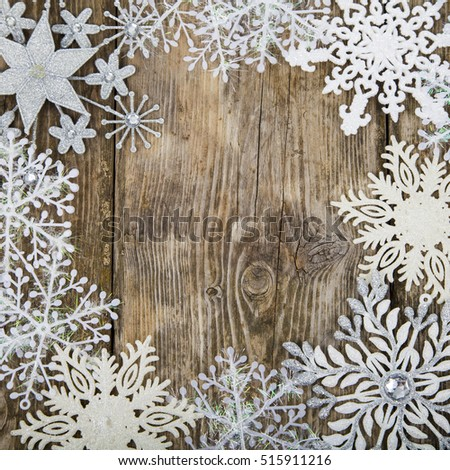 Frame of Christmas snowflakes on old wooden background