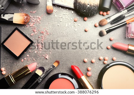 Frame of decorative cosmetics and accessories for makeup on grey background - stock photo