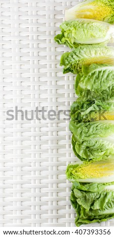 Frame of Fresh Crunchy Romaine Lettuce Full Heads and Halves with Water Drops closeup on Wicker background - stock photo