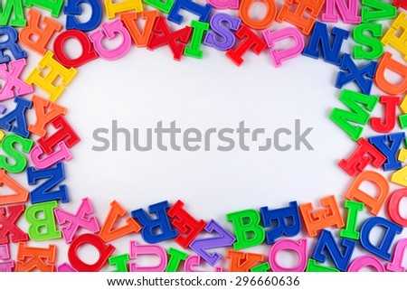 Frame of plastic colorful alphabet letters on a white background