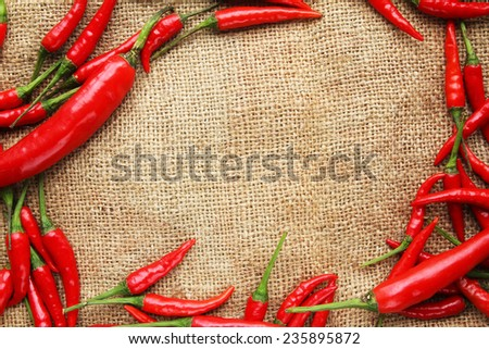 Frame of red chilli peppers on gunny sack texture