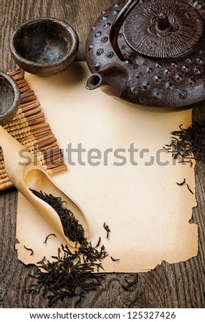 Frame with Asian teapot, dried black tea and vintage paper - stock photo