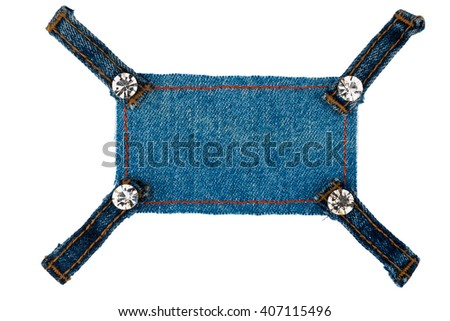Frame with four straps jeans and rhinestones, lies on the dark denim, isolated on white background