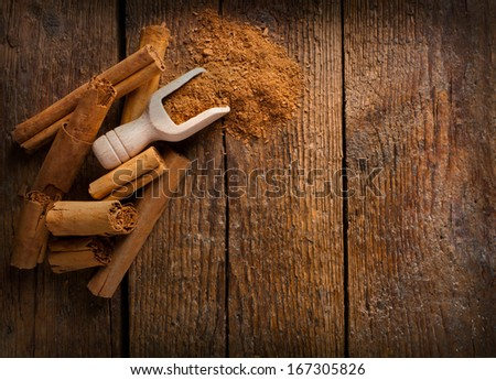 Frame with sticks and ground ceylon cinnamon on wooden table - stock photo