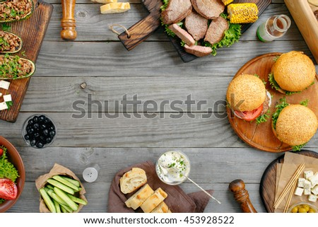 Frame with various foods, grilled burgers, steaks, stuffed zucchini, vegetables and sauces on a rustic wooden table. Outdoors Food Concept. Food background - stock photo