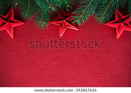 Frame with xmas tree and ornaments on red canvas background. Merry christmas card. Winter holiday theme. Space for text. Happy New Year. - stock photo