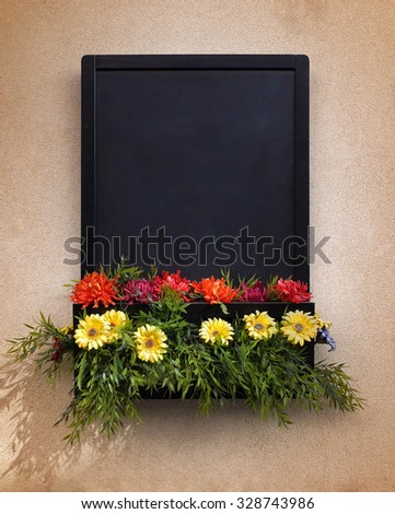 Framed blackboard with copy space and decorated with colorful flowers - stock photo