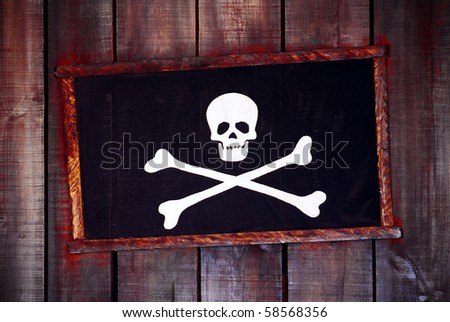 Framed pirate flag hanged in an old wooden wall - stock photo