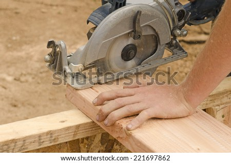 Framing contractor using a circular hand  saw to trim wood studs to length. - stock photo