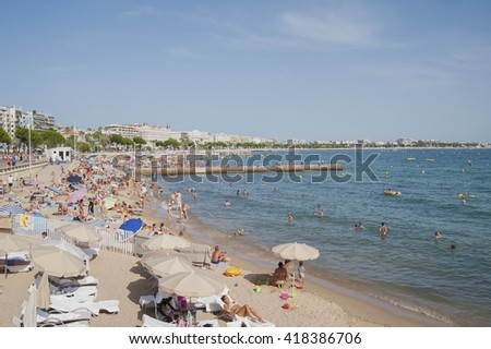 FRANCE, CANNES - AUGUST 6, 2013: A lot of people on the beach of La Croisette. - stock photo