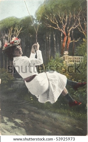 FRANCE-CIRCA 1908: hand-painted photograph of young woman happy smiling on a swing , circa 1908 - stock photo