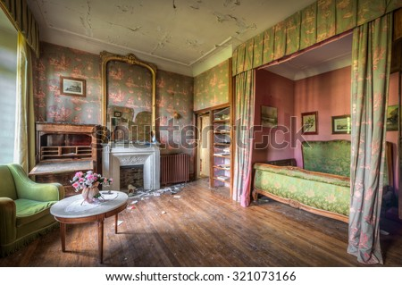 FRANCE - SEPTEMBER 26, 2015: Dilapidated luxurious bedroom in an abandoned castle, somewhere in France.  - stock photo