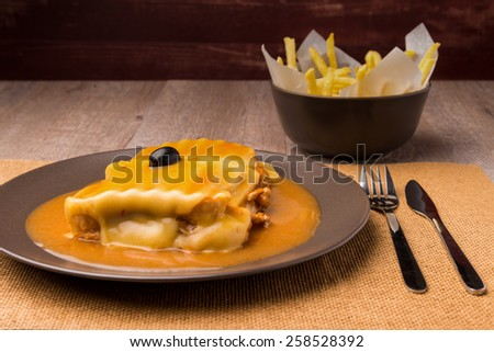 Francesinha and french fries, typical food from Porto, Portugal - stock photo