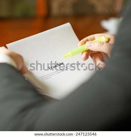 Franchise definition as a shallow depth of field close-up composition of a man in a business suit working with the text - stock photo