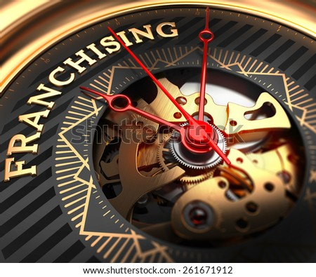 Franchising on Black-Golden Watch Face with Closeup View of Watch Mechanism. - stock photo