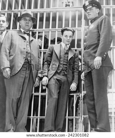Francis 'Two Gun' Crowley (1911-1932), hand cuffed to a law enforcement officer, as he leaves the jail in Mineola, New York.