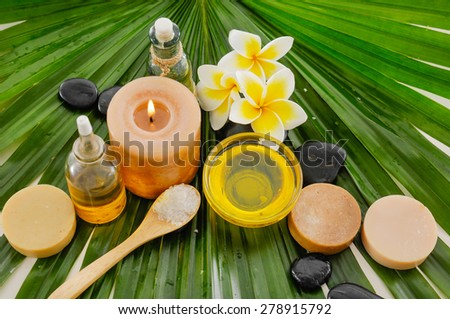 frangipani and candle ,oil ,stone,soap, stones, on palm leaf - stock photo