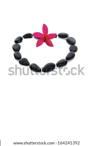 Frangipani and zen rocks arrange in love shape (selective focus and shallow DOF) with white background. - stock photo