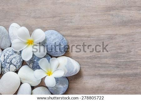 frangipani flower and stone zen spa on wood - stock photo