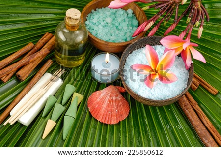 frangipani with oil ,salt in bowl ,oil ,candle ,shell on palm leaf texture  - stock photo