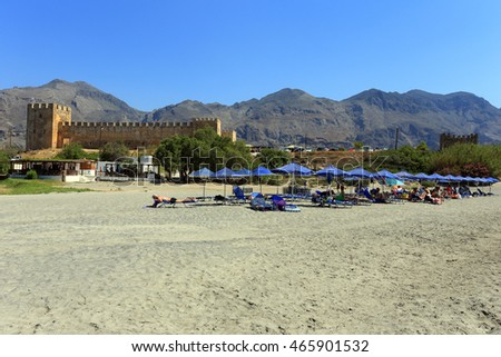 FRANGOKASTELLO, CRETE - JULY 3, 2016: Tourists relax on the beach beside the castle at Frangokastello, south Crete. Visitor numbers on the island were up 12% in July.