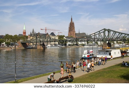Frankfurt, Germany - August 29, 2013: People walk along the river Main with the iron footbridge and Frankfurt cathedral in the background in Frankfurt, Germany on August 29, 2013. - stock photo